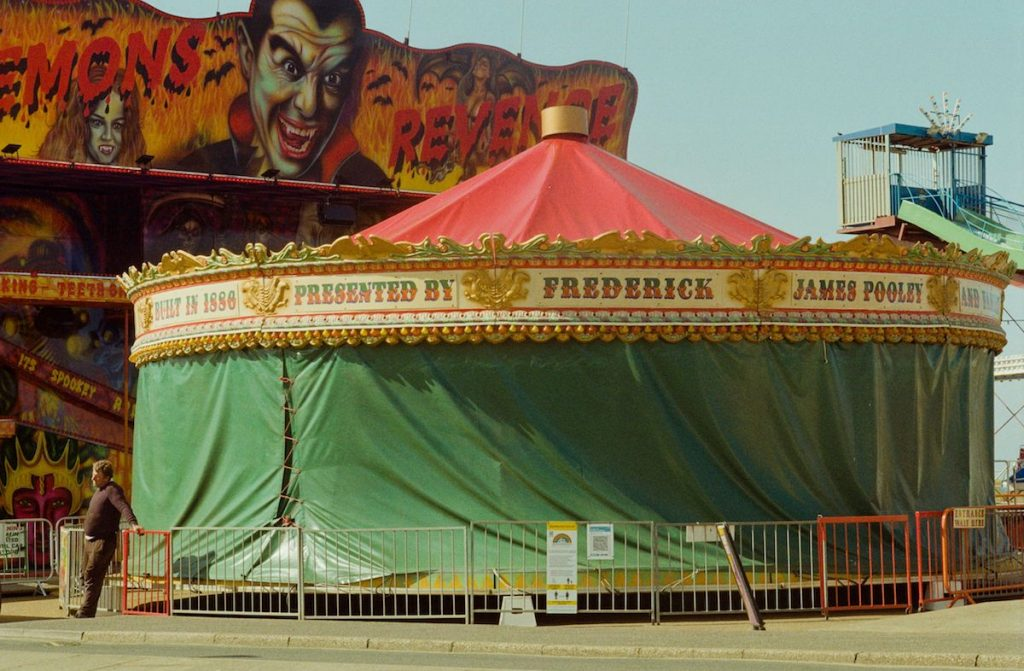 Si Barber - Bela Lugosi looks down on Pooley's Gallopers ride at Hunstanton funfair on Easter Sunday 2021 in Hunstanton. Built by Frederick Savage in 1886 it has only ever been closed twice in the holiday season,  both times in 2020 and 2021 due to the Covid 19 Pandemic - Photograph - 40 x 30 cm - £40